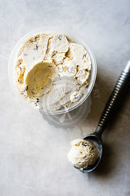 Choc chip ice cream in a tub with scoop