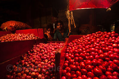 Onions for sale under red lights at the Kole wholesale vegetable market, Bowbazar, Kolkata, India. Kole is one of the largest veg markets in India.