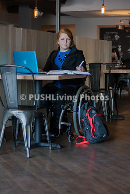 Young woman in wheelchair at computer cafe