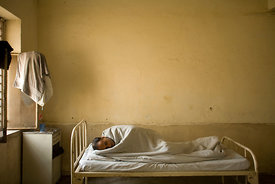 India - Delhi - A mentally ill patient sleeps in his bed on a secure ward