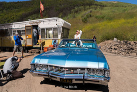 Photographers shoot a model in a 1967 Chevrolet Impala convertible in El Capitan Canyon in California.