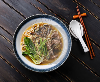 Ramen asian noodle in broth with Beef and pak choi cabbage in bowl on dark wooden background