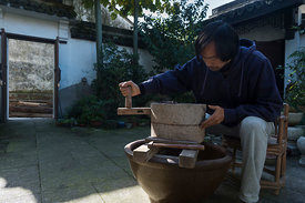 Wu Zhi Qiang, 50, master potter, tea grower and clay expert, hand-grinding Yixing purple clay in courtyard of his house, Shao Wu village in the Guzhu Hills, just south of Dingshu.
