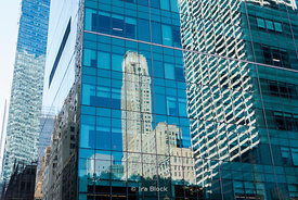 A building reflected on a glass building on 6the Avenue near Bryant Park in New York.