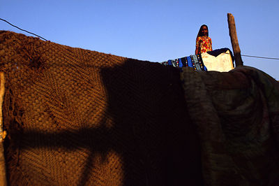 India - New Delhi - A woman on the roof of her shack