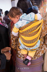 A baby carried with a back cross wrap at Punakha  Dzong festival in Bhutan.