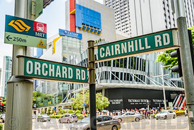 SINGAPORE CITY, SINGAPORE - OCTOBER 09, 2016:  A street sign at the junction of Orchard Road and Cairnhill Road in central Singapore.  Orchard Road is a busy retail street with upmarket stores.