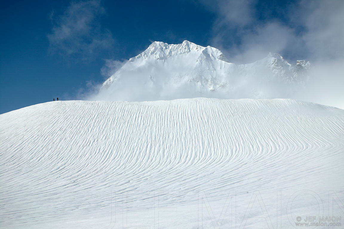 Skiers on ridge and rain-created snow patterns