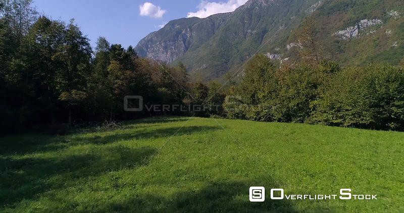 Mountain town, C4K aerial rising drone view over trees, revealing a small alpine town, near soca river, on a sunny summer day, in the Julian alps, Slovenia