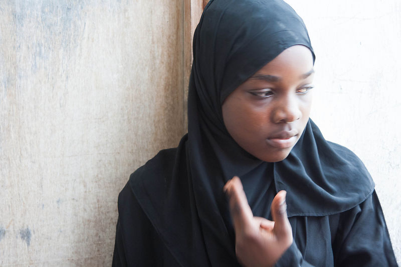 Fatmata Abdulrahman Mbamba, 13, stands in front of the door to her apartment in Michinzani, Stone Town Zanzibar.