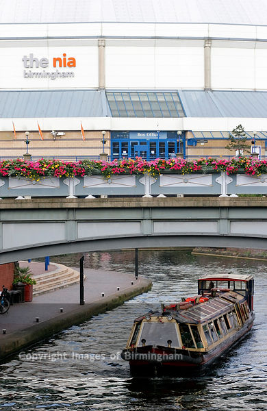 Canals and The NIA (National Indoor Arena). Birmingham, UK.  The exhibition and sporting venue. Canal barge in front.