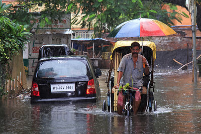 A rickshaw driver plies his trade during monsoon flooding, Lake Gardens, Kolkata, India. Taken during the heaviest rains in Kolkata in a decade.
