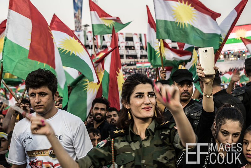 A woman dances amid waving flags at the final pro Kurdish independence rally, held at the Franso Hariri Stadium in Erbil. 22nd September 2017. Elizabeth Fitt