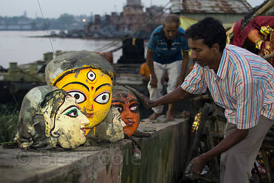 Painted ceramic heads from Hindu idols are reclaimed after being pulled from the Hooghly River, Babughat, Kolkata, India. The idols are immersed in the river during the Durga Puja festival, then immediately pulled out by workers to avoid polluting the river.