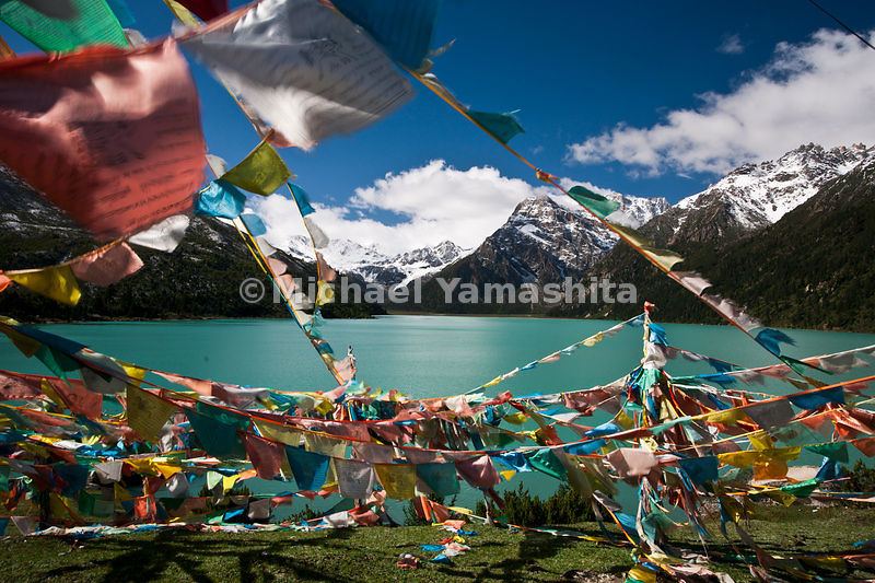 Prayer flags fly over the turquoise waters of the Sacred Lhamo Latso Lake.