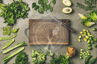 Healthy vegan ingredients and wooden board and knife in center