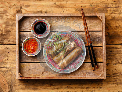 Spring rolls with sauce in wooden tray on wooden background