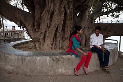 India - Chandannagar - A young couple sit and talk together on the Strand by the Hoogley River, Chandannagar at dusk