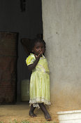 Pretty African girl standing in doorway to house wearing yellow dress, western Kenya Africa