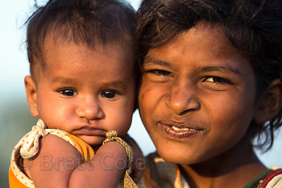 Happy girl and her baby sister in Pushkar, Rajasthan, India