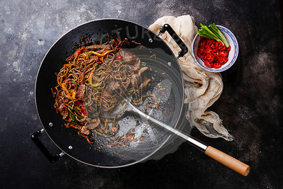 Stir-fry soba noodles with beef and vegetables in wok pan on dark background