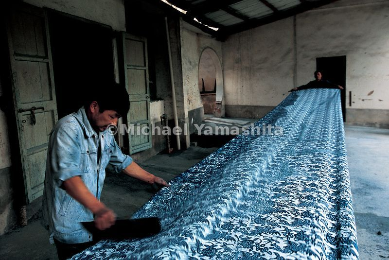 Hot was is applied to cotton fabric in designs and patterns and then dipped in dye. Here a worker scrapes wax off the dyed cotton.