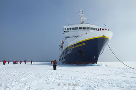Passengers from National Geographic Explorer walk on fast ice along the Antarctic Peninsula.  The ship has wedged itself into fast ice.
