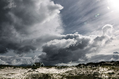 Cape dutch house alone on the beach, big storm clouds behind
