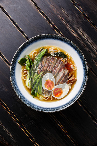 Ramen noodles with Duck, egg and pak choi cabbage in bowl on wooden background close-up