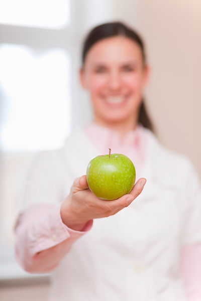 Smiling doctor offering green apple
