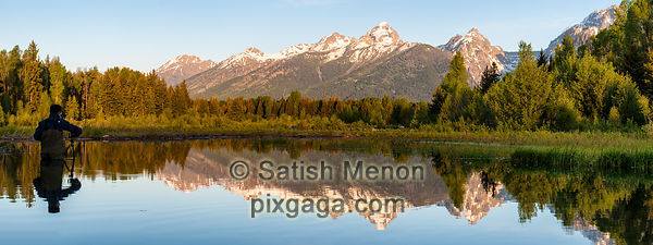 Photographer photographing Grand Teton Range and reflection, WY, USA