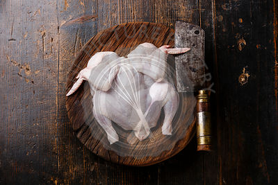 Raw whole chicken on wooden background