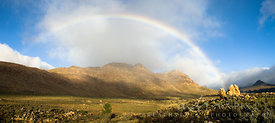 Rainbow over a valley and mountains (Apollo and Luna Peaks) with rocks and fynbos vegetation in the foreground