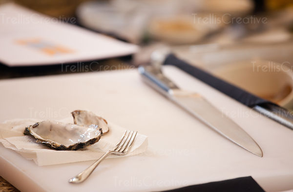 Empty oyster shells on a white cutting board