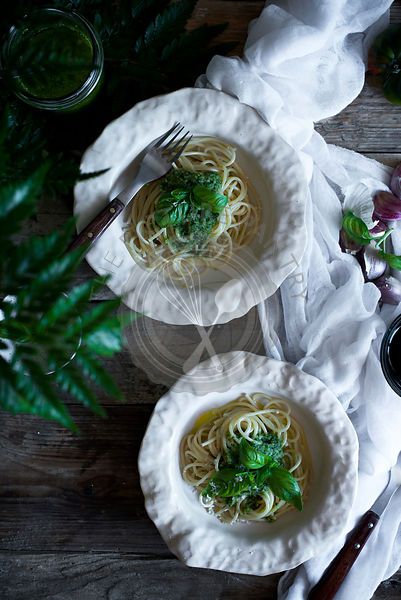Spaghetti with pesto and decorated with basil leaves