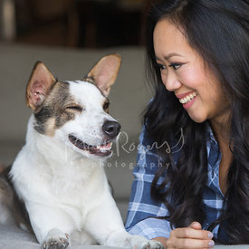 Young Asian Woman Smiling at Happy Dog
