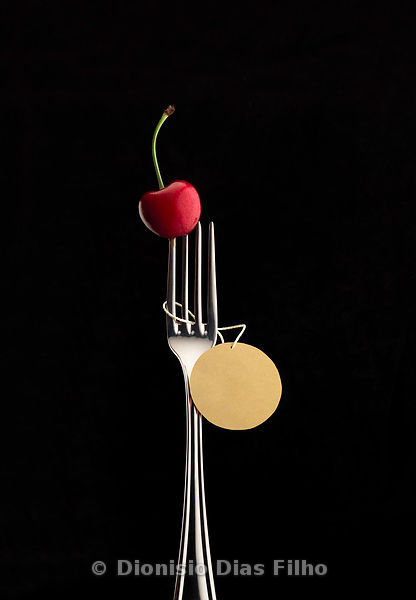 Fork with spiked cherry and round label hanging on black background