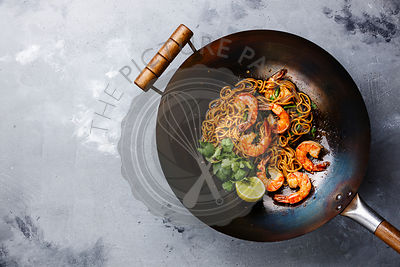 Ramen stir-fry noodles with shrimp in wok pan on gray concrete background