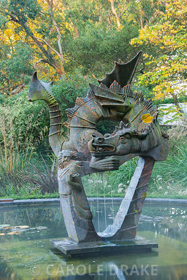 Dragon sculplture forms a centrepiece in the Dragon garden surrounded by beds brimming with grasses and perennials. Knoll Gardens, nr Wimborne, Dorset, UK