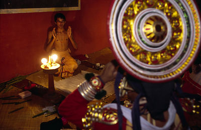 India - Kerala - A student helps an actor centre his elaborate headress before a performance