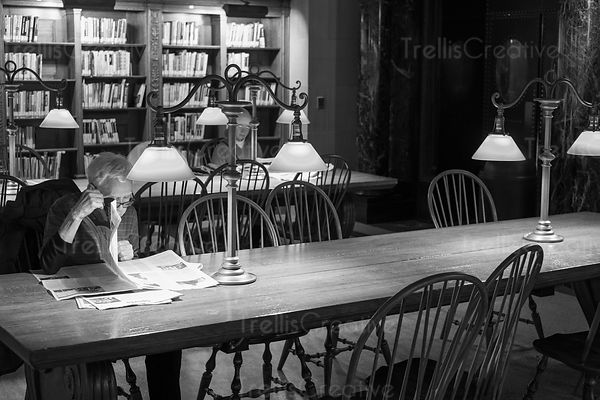 Black and white shot of a senior man reading newspaper in New York Public Library