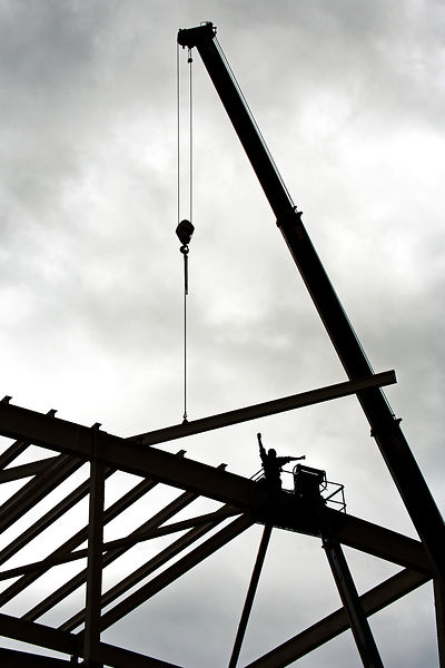sillhouette against a dark sky of a steel erector in a cherry picker on a building site
