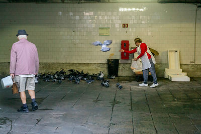 A woman feeds pigeons at the Mercado do Bolhão, Porto, Portugal.