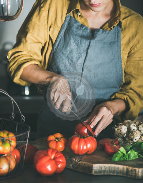 Woman cutting and cooking tomato sauce or pasta