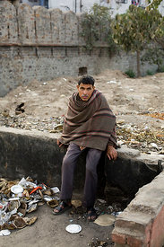 India - Delhi - A homeless mentally ill man sits alone on a low wall