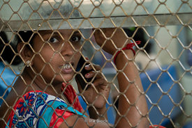 A passenger looks out the window of a local train at Chhatrapati Shivaji Terminus in Mumbai, India
