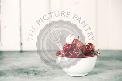 Fresh cherries in bowl on a rustic background