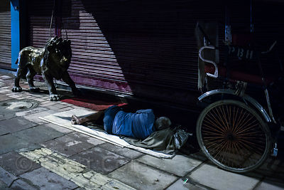 A cycle rickshaw driver sleeps on the street in Delhi, India. Many if not most cycle rickshaw drivers are homeless.