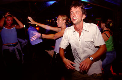 Young travellers dance at a bar