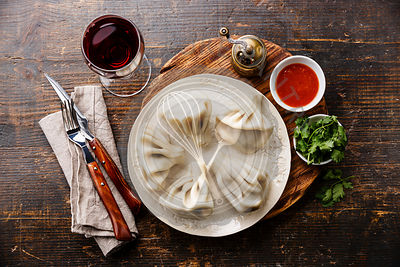 Georgian dumplings Khinkali with meat and tomato spicy sauce on white plate and wine